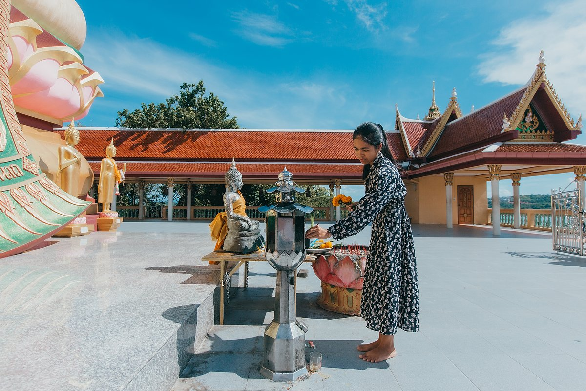 Eie Frau entzündet eine Kerze auf der Plattform des Big Buddha auf Koh Samui