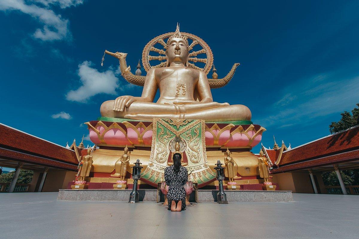 Eine Frau kniet betend vor der Big Buddha Statue auf Koh Samui