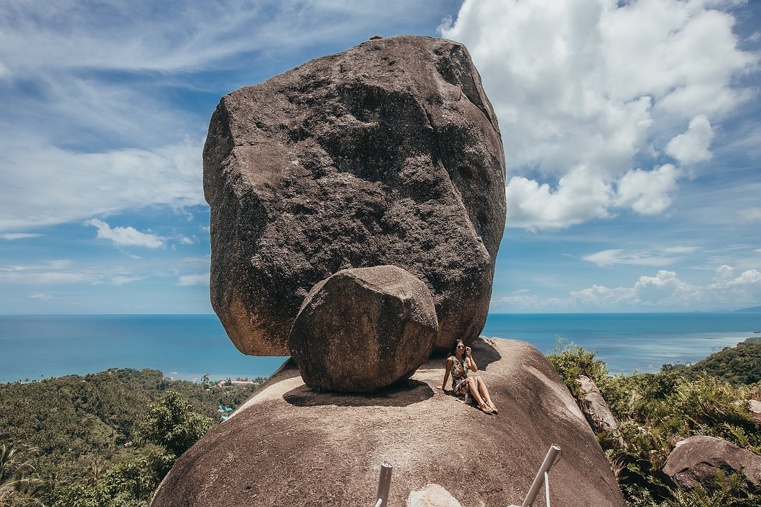 Eine Frau sitzt auf dem Felsen des Overlap Stone Koh samui