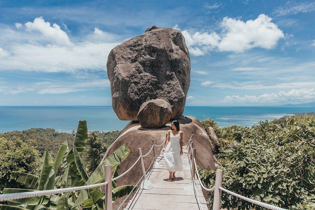 Vorderansicht des Overlap Stone Koh Samui. Frau im weißen Kleid steht auf der Treppe