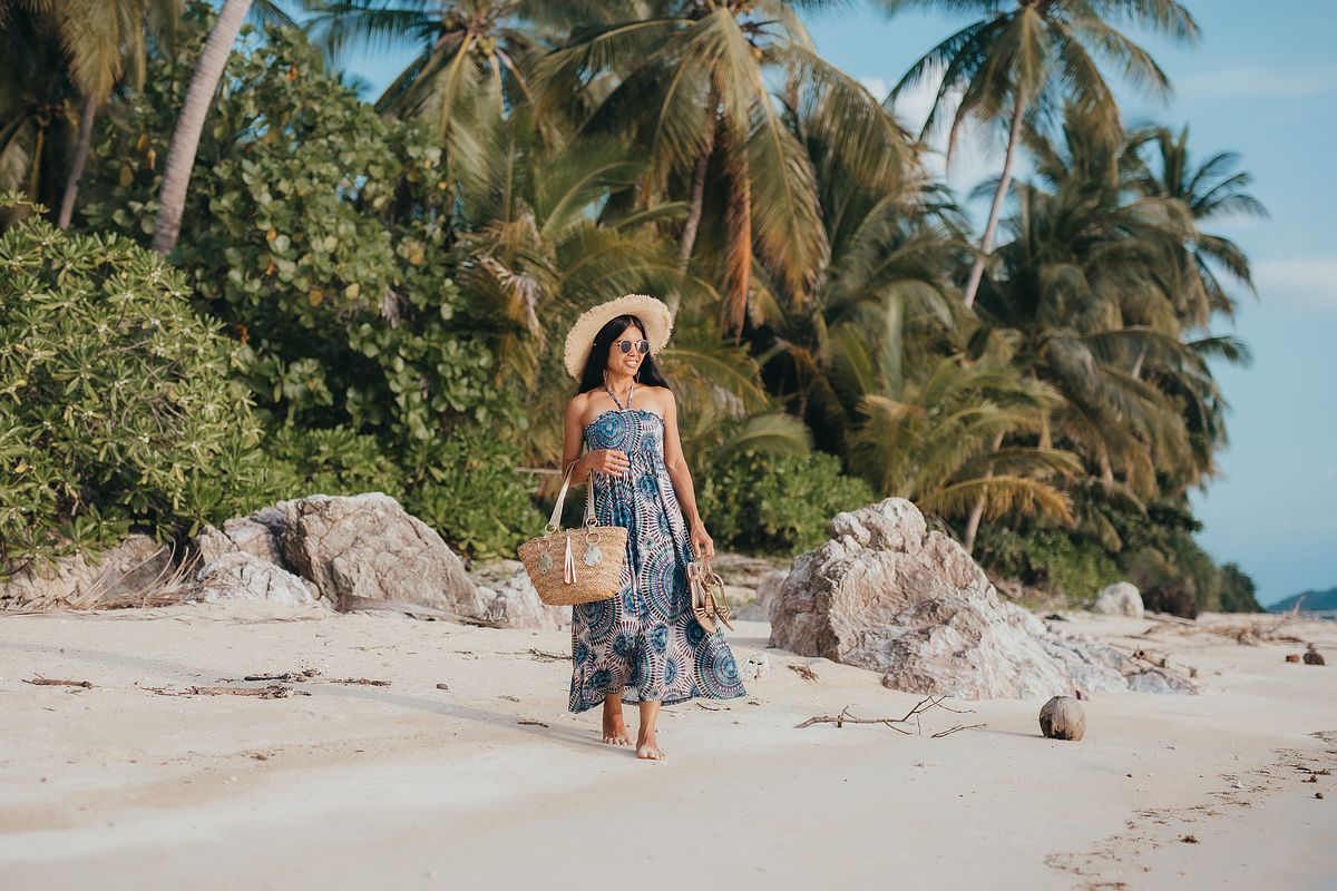 Taling Ngam Beach Koh Samui. Eine Frau spaziert im Strandkleid über den Strand