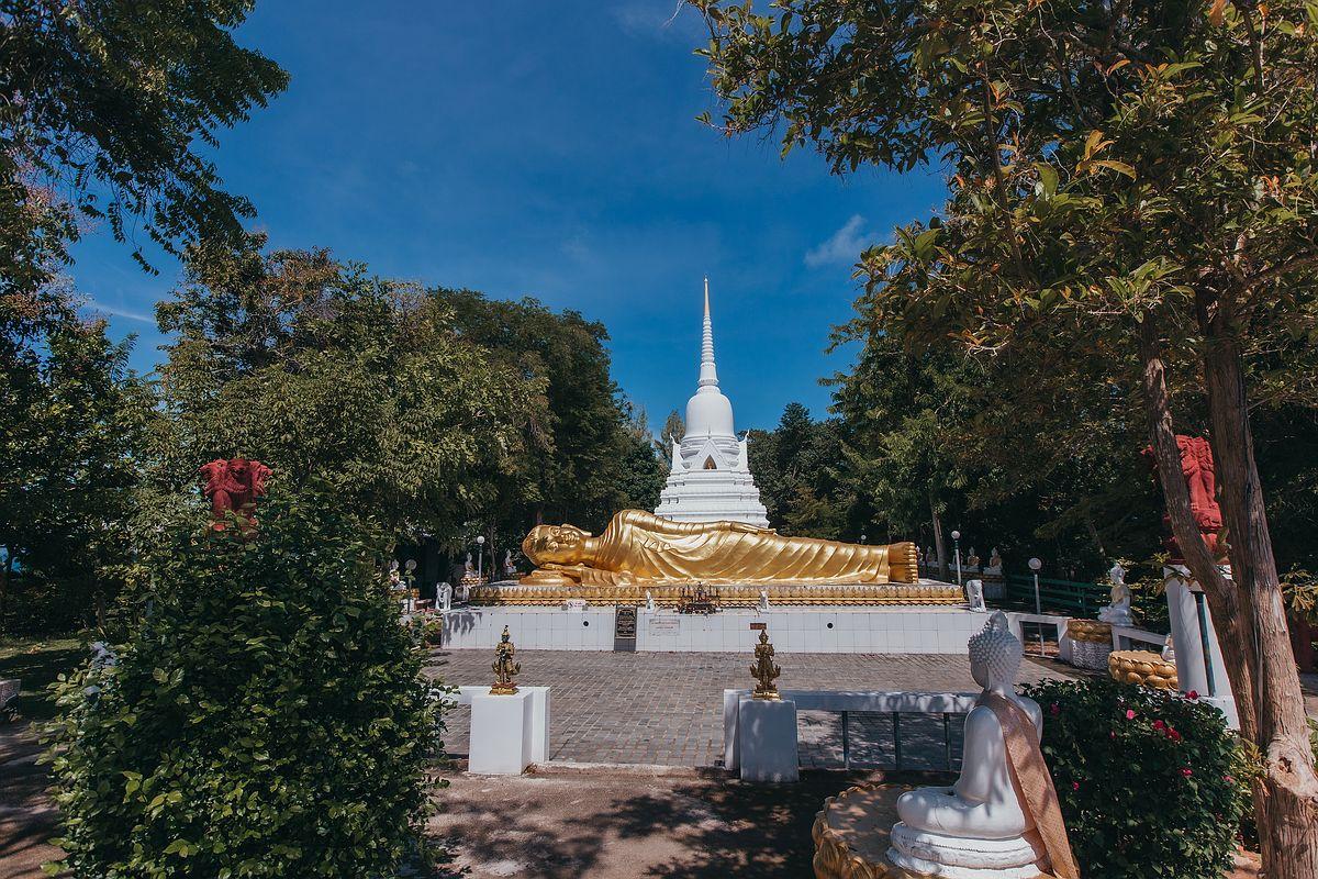 Wat Khao Chedi Tempel Koh Samui - Vorderansicht einer goldenen Buddha Statue die vor dem weißen Chedi ruht