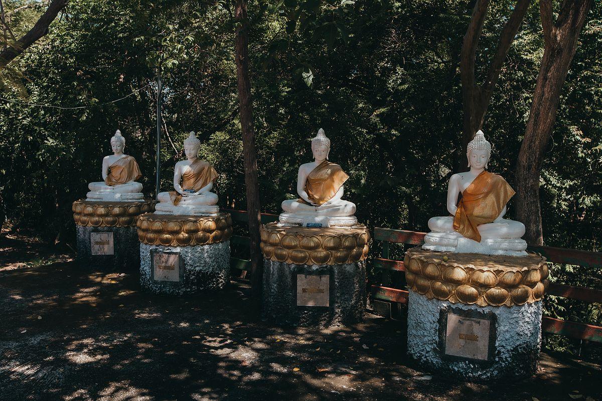 Vier weiße Buddha Stauuen mit goldenen Tüchern